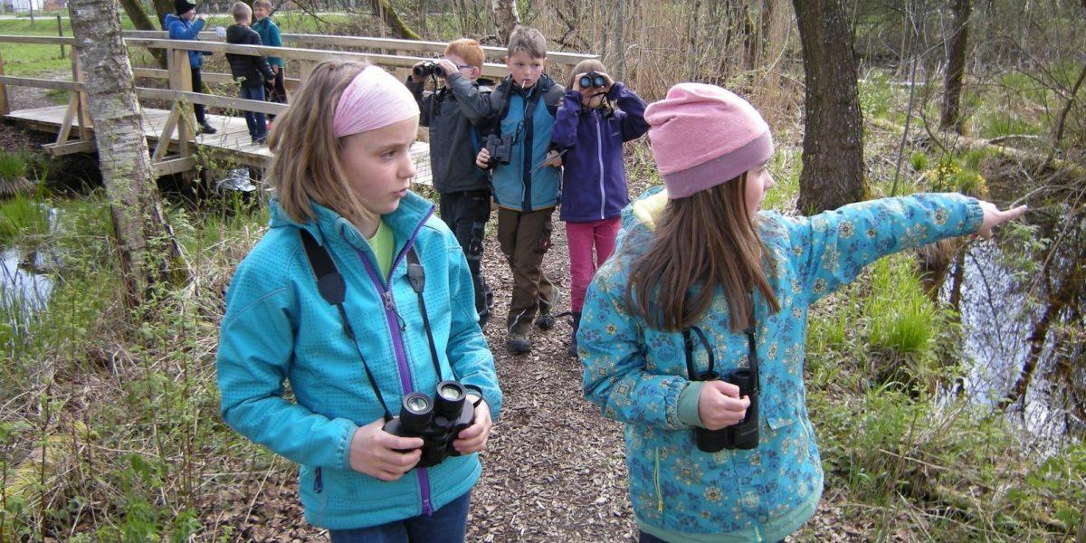 Kinder der Natur-Kindergruppe mit Ferngläsern im Pfrunger-Burgweiler Ried